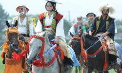 A young woman (C) clad in samurai costume leads other local poeple as she rides her horse during a parade at the annual Soma Nomaoi festival in Minamisoma, Fukushima Prefecture, on July 28, 2012.  The traditional full-scale festival kicked off for the first time after the accident of the Fukushima Dai-ichi Nuclear Power Plant following the massive earthquake and the tsunami on March 11, 2011.    AFP PHOTO/Toru YAMANAKA